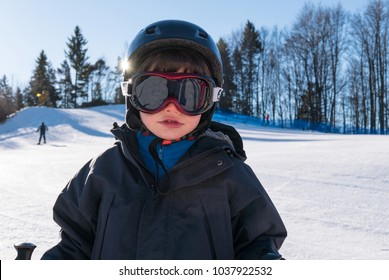 Young kid having fun in the snow skiing. Close up portrait.