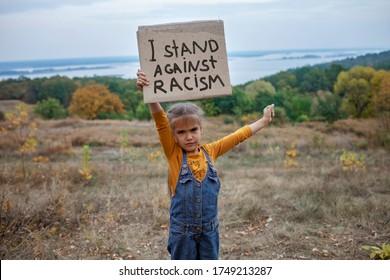 Junge Kinder, die ein Poster mit einer Anti-Rassismus-Botschaft auf schönem Naturhintergrund halten, Aktivismus und Menschenrechtsbewegung, Outdoor-Lifestyle