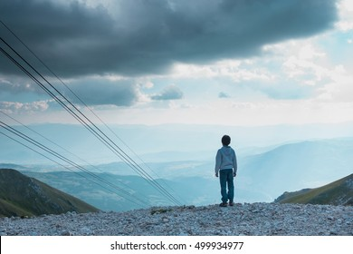 Young kid looking at panorama from Campo Imperatore plateau. Gran Sasso, Italy. Conceptual image for future generations expectations.