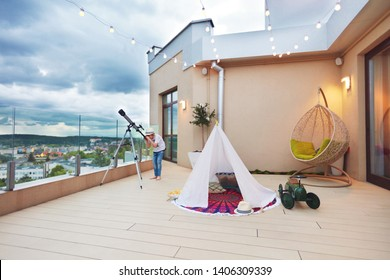 young kid looking in telescope while playing games on rooftop patio