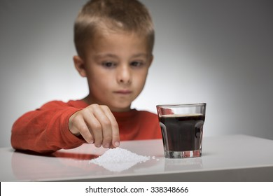 Young kid looks in front of sugar sweetened soft drink. The over-consumption of sugar-sweetened soft drinks is associated with obesity, type 2 diabetes, dental caries, and low nutrient levels.