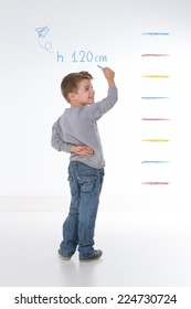 young kid measures his own height on the wall