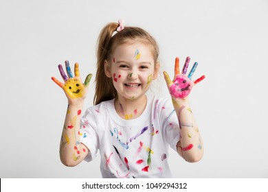 Young kid in messy t-shirt showing her colorful hands. Messy and creative fun.