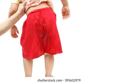 A young kid peeing on his shorts - Bed-wetting concept with white space to add text