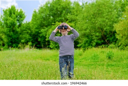 Young kid playing with binoculars on a sunny day.