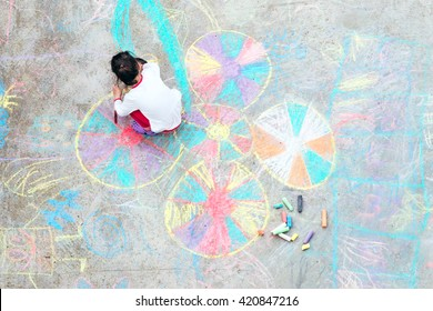 Young kid playing with chalk.