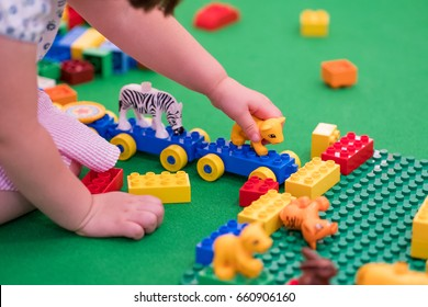 Young kid playing with colorful bricks.