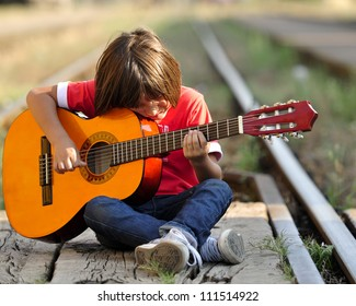Young kid playing guitar on railroad