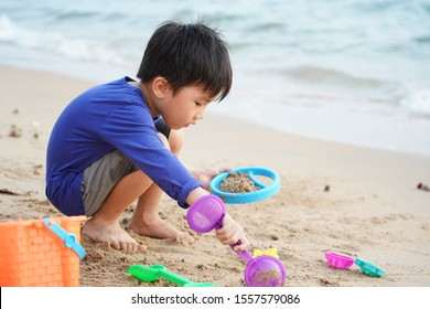 YOUNG KID PLAYING WITH SAND AT BEACH