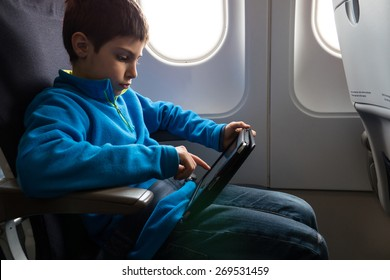 Young kid relaxing using tablet inside airplane.