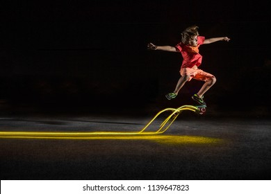 A young kid riding scate with light at night