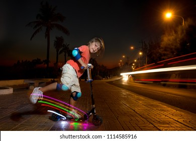 A young kid riding scooter with light at night