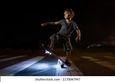 A young kid riding skate with light at night