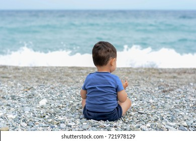 Young kid sitting on the pebbles, looking at waves