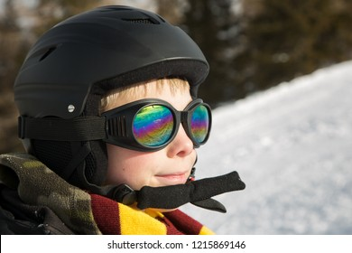 Young kid with ski sport helmet and glasses outdoors, at winter time.