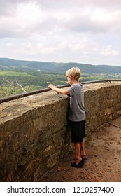 A young kid is standing on his tiptoes, holding onto a railing and looking over a cliff on a scenic overlook in s small midwestern American town on a summer day.