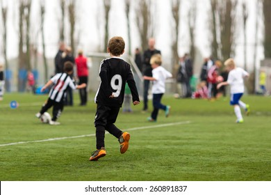 Young kids during a boys soccer match on green soccer pitch.