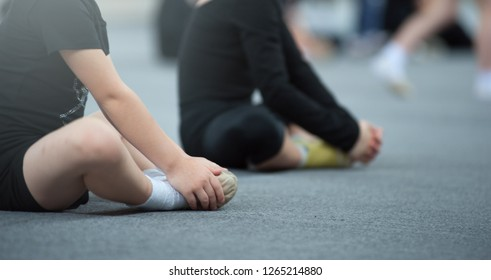Young kids gymnast doing stretching exercises sitting on the floor dressed in black leggins. During stretching exercises for little kids in the sports club