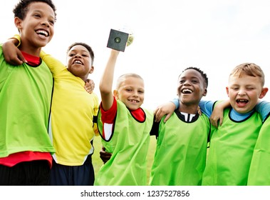 Young kids on the field celebrating their victory