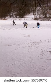 young kids playing ice hockey outside on frozen pond
