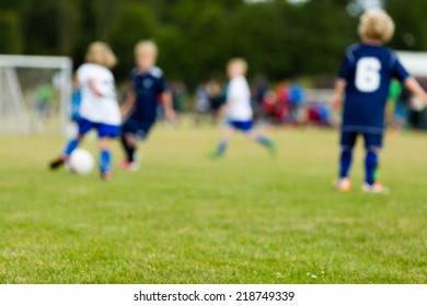 Young kids playing soccer outside during summer time. All players are blurred.