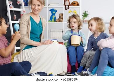 Young kindergarten teacher playing music with little kids