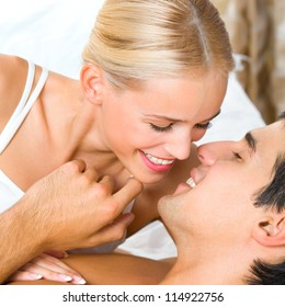 Young kissing cheerful attractive couple on bed