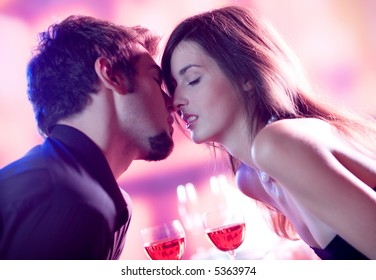 Young kissing couple celebrating with red wine together