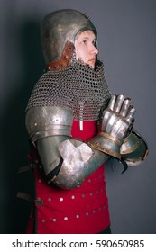 Young knight in armor of the 14th century, with a sword. Studio photo, gray background. Helmet bascinet, brigantine, armor.