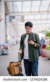 A young Korean Asian man is booking a ride on his ride-hailing app on his smartphone. He is waiting at the cab stand in the airport with his luggage. He is casually dressed and excited about his trip.