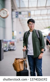 A young Korean Asian man is waiting for his ride that he booked on his ride hailing app via his smartphone. He is casually dressed and standing at the cab stand at the airport with his luggage.