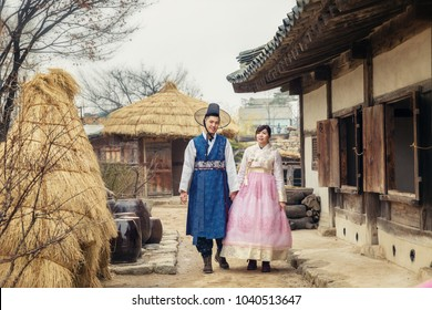 Young Korean couple in hanbok wolking in the park