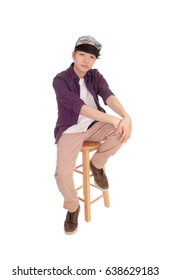 A young Korean teenager sitting on a chair with a cap with hishands on his knee, isolated for white background.