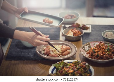 young korean woman put foods on table for family