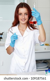 Young lab technician holds tube with red liquid, lab shoot