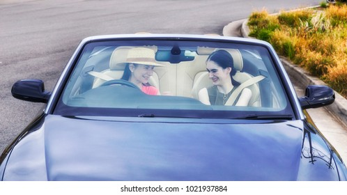 Young ladies driving a modern luxury convertible car with soft top down on a sunny summer day full of joy and happiness - seen through windscreen.