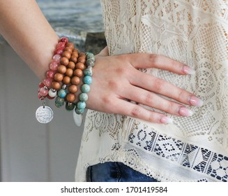 Young ladies hand resting on hip and showing off her stacked bohemian style bracelet set. 5 wooden and turquoise beaded hobo bracelets with silver charm