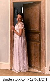 Young lady in authentic regency dress standing in a doorway