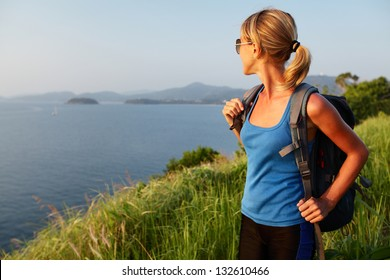 Young lady with backpack standing on a lush tropical meadow and looking to horizon