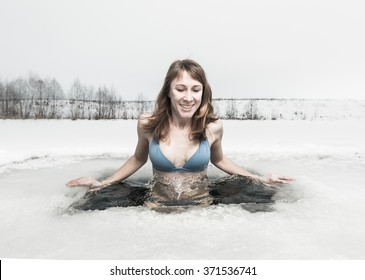 Young lady bathing in the ice hole