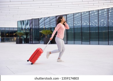 Young lady being late for boarding plane. Indian girl running over airport and talking on phone. Departing flight concept