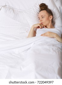 Young lady between 30 and 40 years old stays in her bed. Closeup
