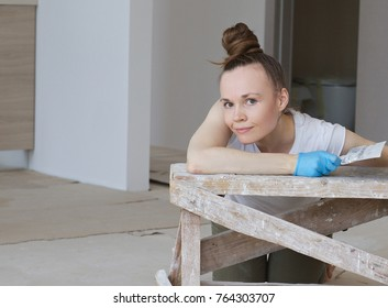 Young lady between 30 and 40 years old is renovating apartment.