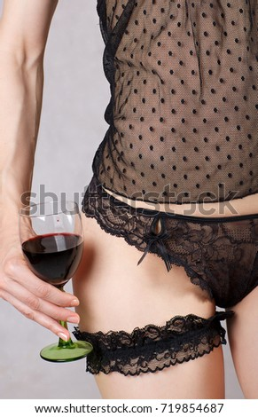 3d19d4098 Young lady between 30 and 40 years old dressed in lingerie keeps a glass of  red