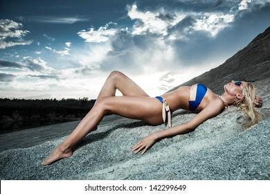 Young lady in bikini lying on sand rocks