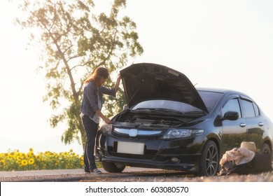 A young Lady with a black car that broke down on the road. Making telephone call to get help with the broken car.