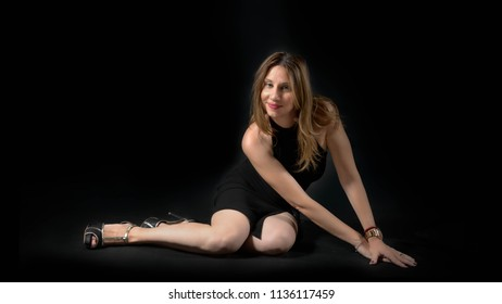 young lady in a black mini dress, posing on floor against a dark black background