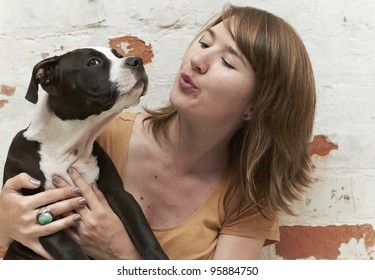 Young lady blowing air into face of Pit Bull puppy
