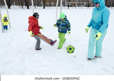 A young lady in a blue ski suit plays football with children in the snow. Yellow sled, sunglasses, bright clothes. Girl happy outdoors. Fun winter vacation for the whole family. Green soccer ball