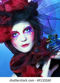 Young lady with bright make-up in doll-style with glass box and beads in it